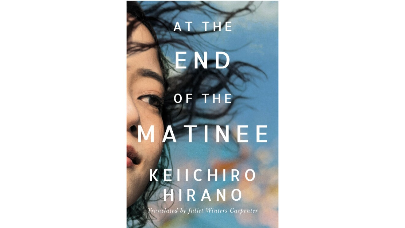 """The book cover of """"At The End Of The Matinee by Keiichiro Hirano"""" features a woman with dark hair blowing in her face looking out into the distance. The blue sky consumes the rest of the cover."""