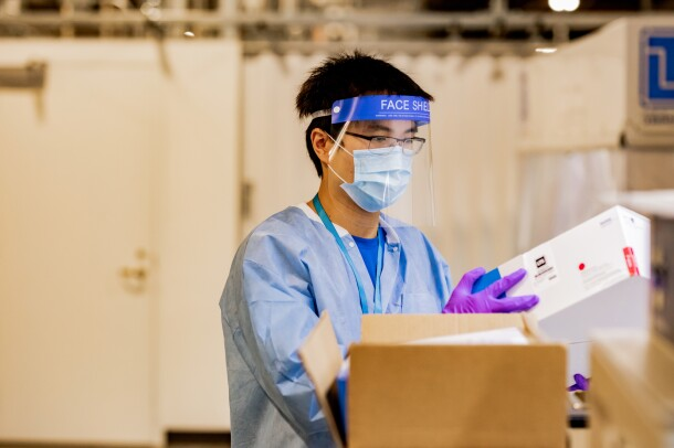 A man wears a face shield, gloves, mask and PPE while handling boxes
