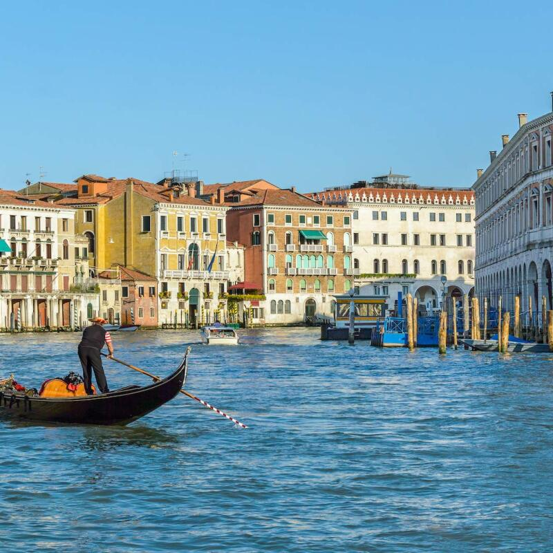 An image showing a large body of water with a person standing in a boat while rowing it. Buildings from an Italian city surround the water.