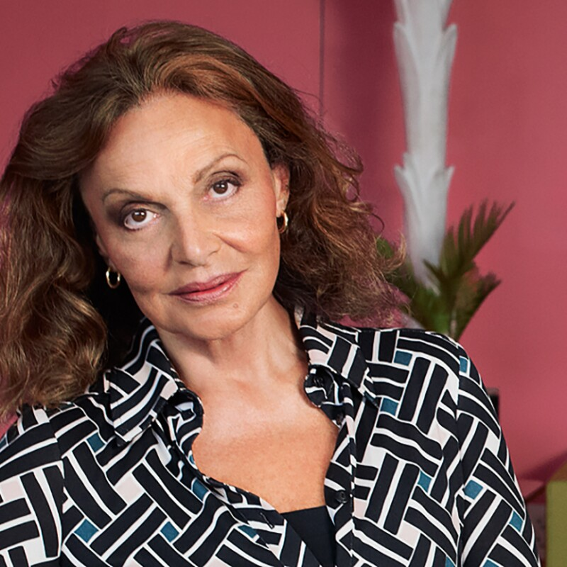 Diane von Furstenberg wears a button down top and gold hoop earrings, and looks at the camera in a red-hued room