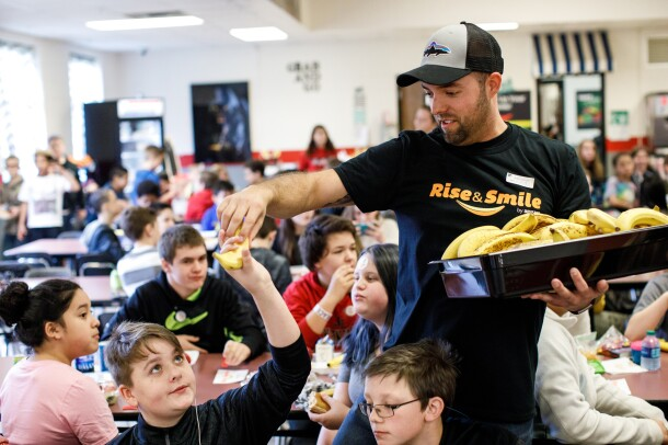 A man holds a tray of bananas and wears a Rise & Smile tee as he hands a banana to a student at a school