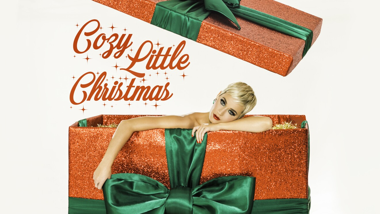 Katy Perry looks at the camera, draped against the top edge of a Christmas gift box.