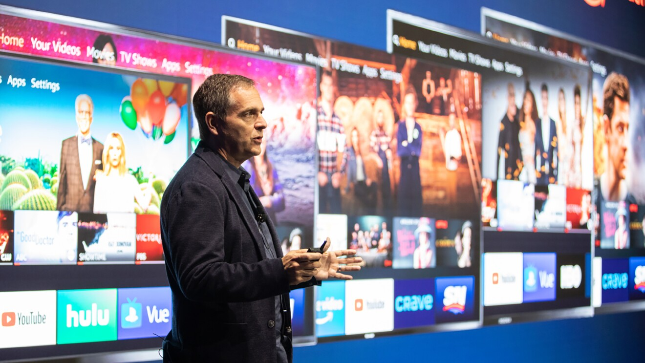 A man stands in front of a screen displaying Fire TV edition displays.