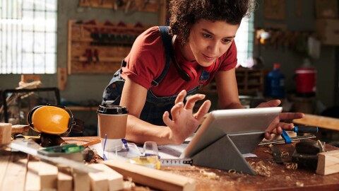 A woman in a wood working space works on a tablet.