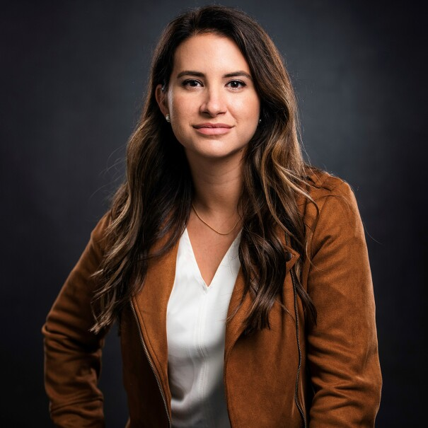 An image of Allie Miller, a White woman with long brown hair wearing a white T-Shirt and a tan jacket.