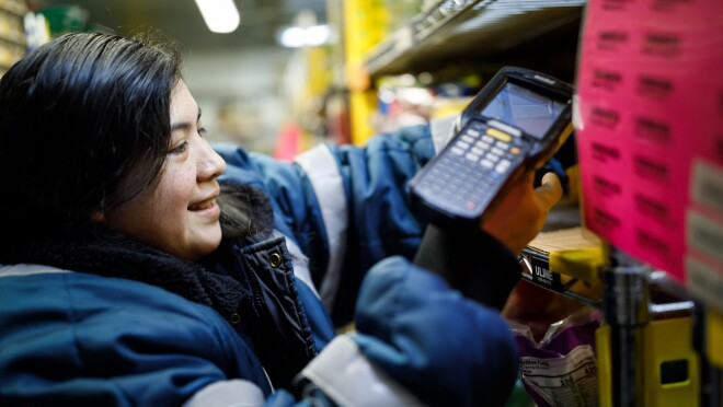 Prime Now associate Erika Lopez scans an item at the Prime Now facility in Seattle, Washington. She is wearing outerwear for comfort while she retrieves items from the facility's freezer and refrigerator spaces.