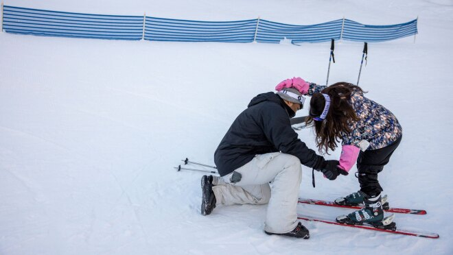 A father helps his young daughter click her ski boots into her skis.