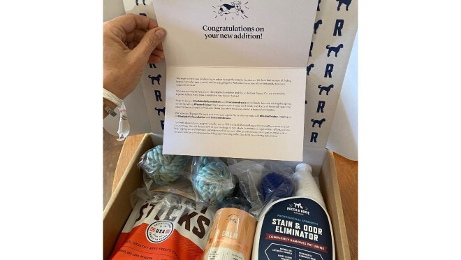 """The Rocco & Roxie boxes the new puppy parents received when adopting their  dog is filled with jerky sticks, a calming supplement, toys and a stain and odor eliminator. There is also a note that reads at the top, """"Congratulations on your new addition!"""" with a picture of a dog."""