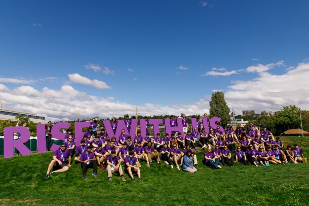 """Dozens of Amazonians in purple tees, pose on a hillside with giant letters that spell out """"rise with us,"""" in support of the Special Olympics USA Games in Seattle, Washington."""