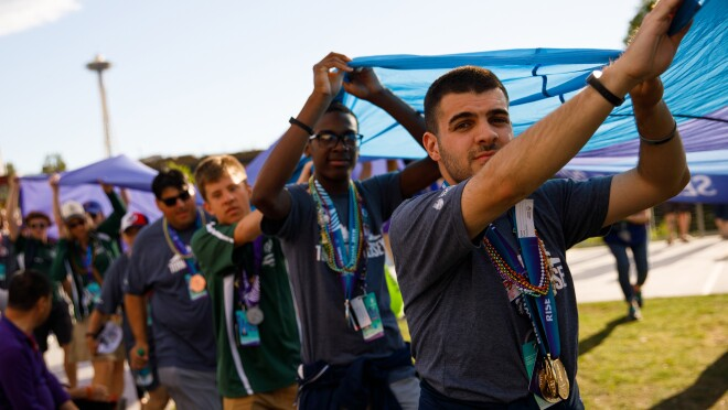 Special Olympics athletes are seen in the foreground and background, as they carry the ceremonial Special Olympics flag during the closing ceremony. Many of the athletes are wearing medals from the games, in the photo.