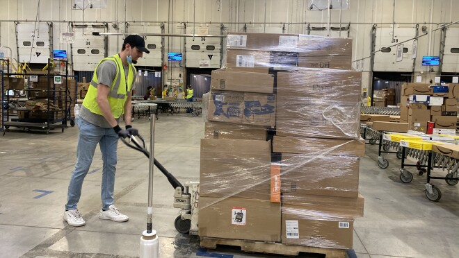 A man moves a pallet of goods.