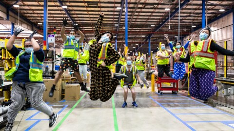 Several Amazon employees wearing pajamas at work leap in the air at a Fulfillment centre. They are celebrating Amazon Goes Gold. All employees wear a safety vest and face mask.