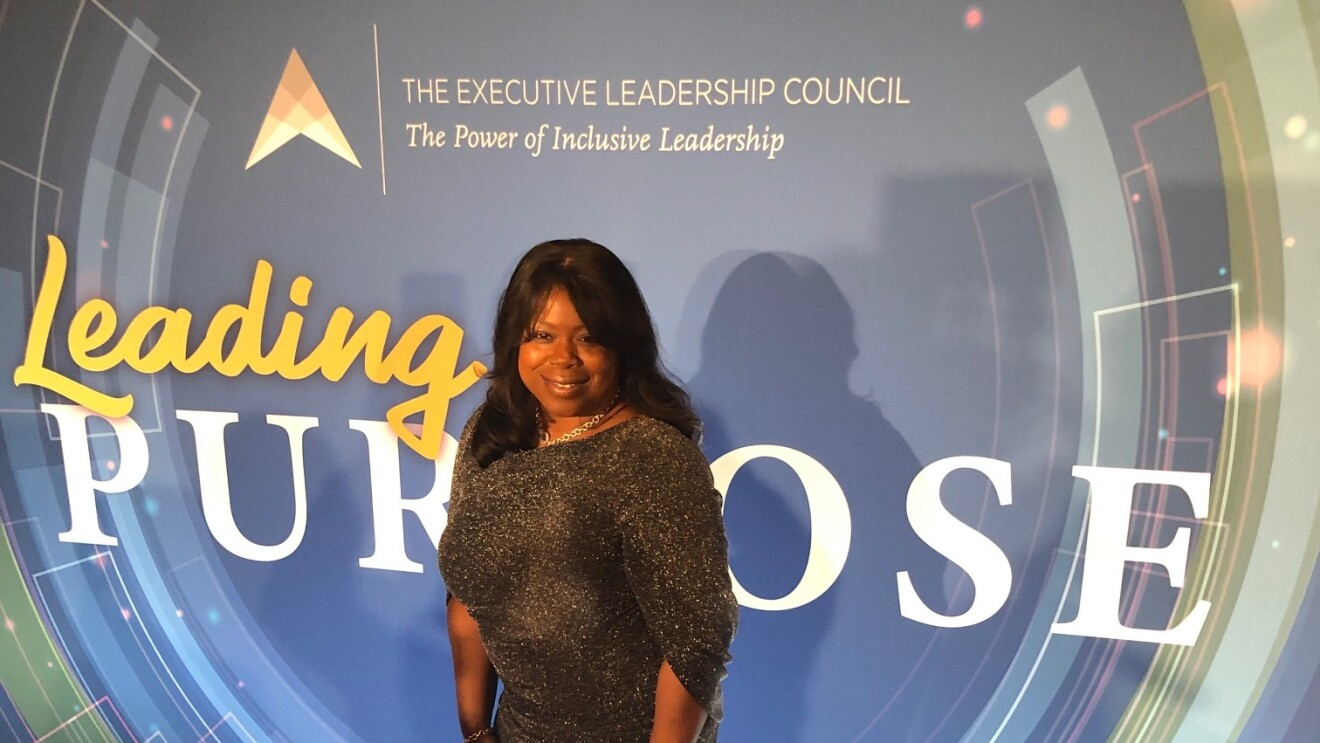 """Nancy Dalton smiles for a photo on a red carpet in a long, sparkling gown in front of a backdrop that says """"Leading Purpose."""""""