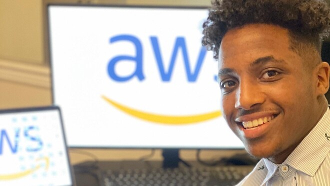 An image of a man smiling while sitting at a desk. He has two computer monitors in the background. both with the AWS logo on the screens.