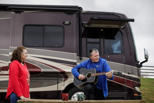 Flanked by a motorhome, a woman watches a man play guitar.