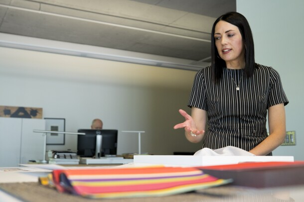 A woman in a grey-striped shirt stands over architectural designs. Her colleague is in the background at a computer.