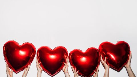 Four pairs of hands hold up heart-shaped balloons.