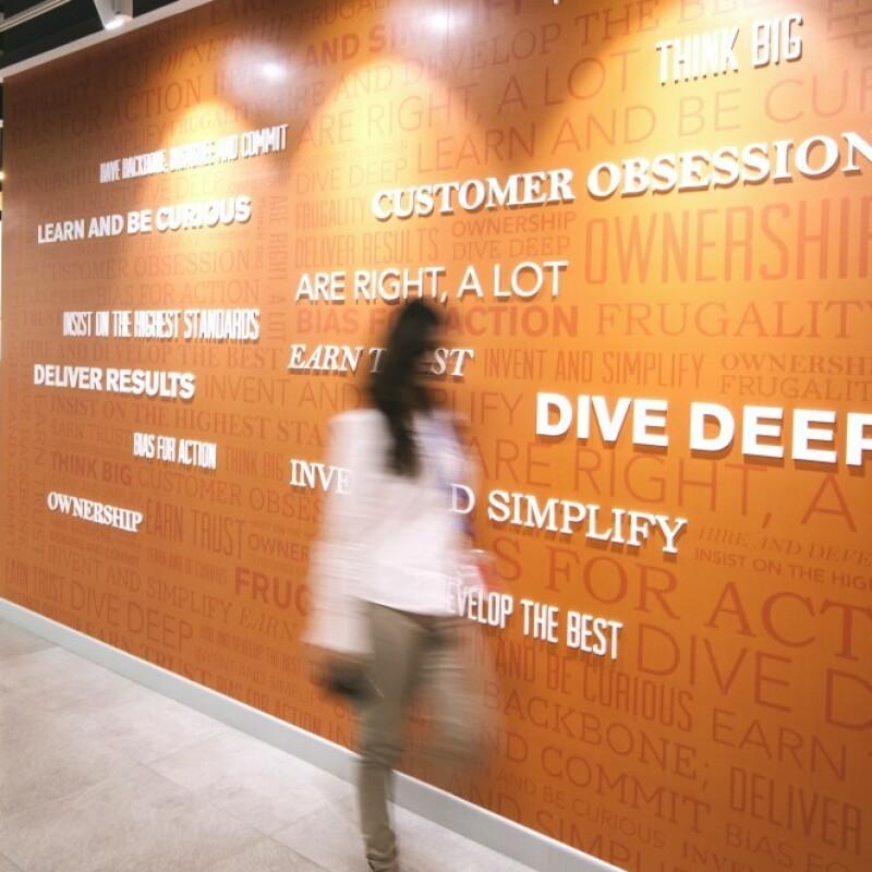 A woman walks past a wall featuring Amazon leadership principles