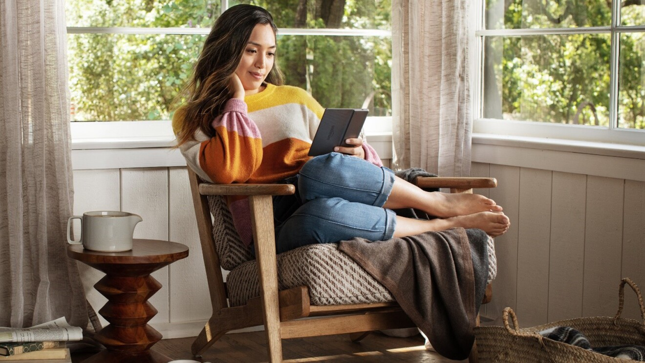 A woman lounges in a chair, with her feet tucked to the side, reading a new Amazon Kindle Paperwhite.