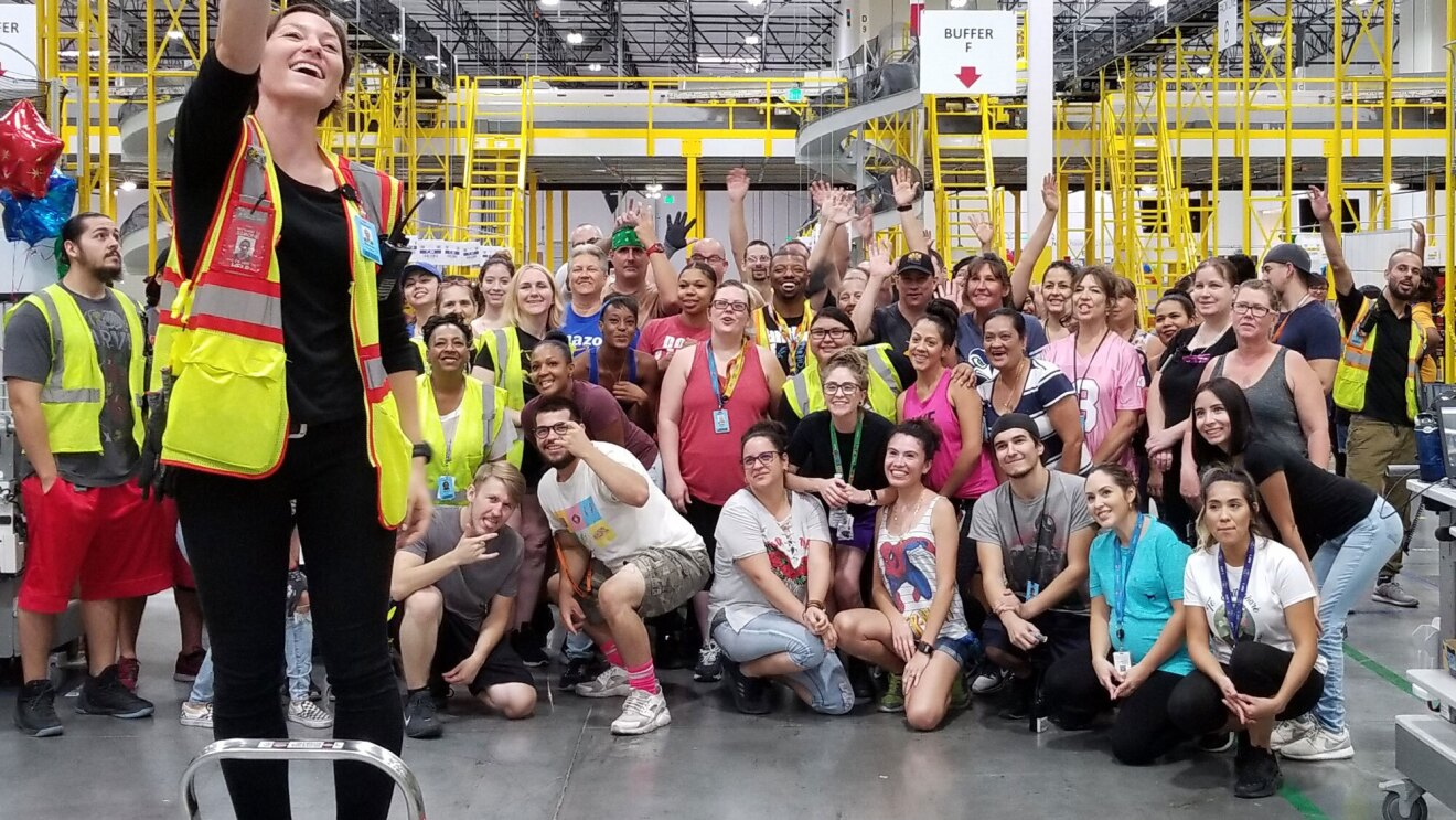 An Amazon associate stands on a step stool, with her arm extended, holding her iPhone in order to capture a selfie. Behind her, dozens of Amazon associates pose for the photo.