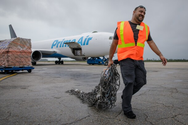 Abe Diaz of the Disaster Relief by Amazon team hauls cargo netting across the tarmac at Lynden Pindling International Airport in Nassau.