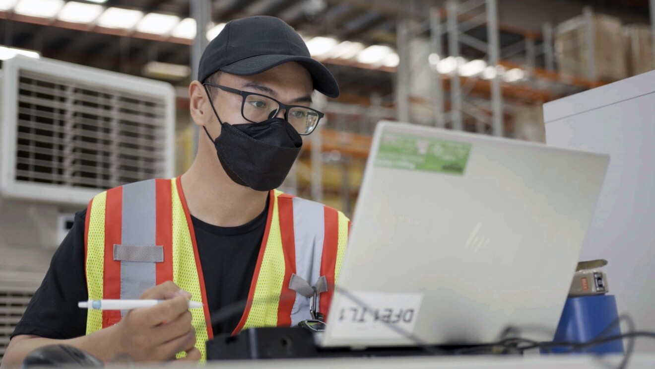 Amazon associate Muhammad Izuan Khairudin is seen working on his laptop at Amazon's Fulfillment Center in Singapore