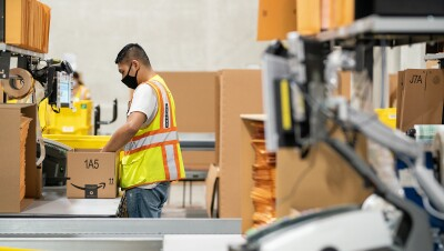 Ops employee with a face mask, packing an order in the Singapore fulfillment centre