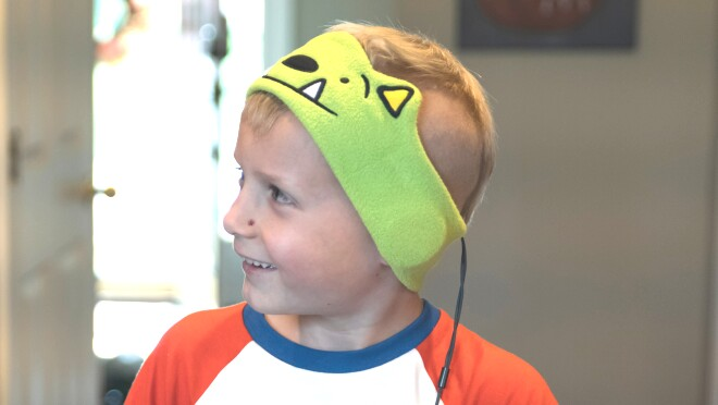 A smiling child wearing headband-style headphones.