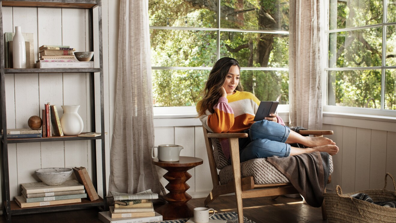 A girls reads on her Kindle from the comfort on her home snuggled on a chair by the window