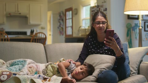 A woman sits on a sofa, with her hand on a child who is laying down on a sofa. The woman looks at her phone as she is seeking medical care for her ill child.