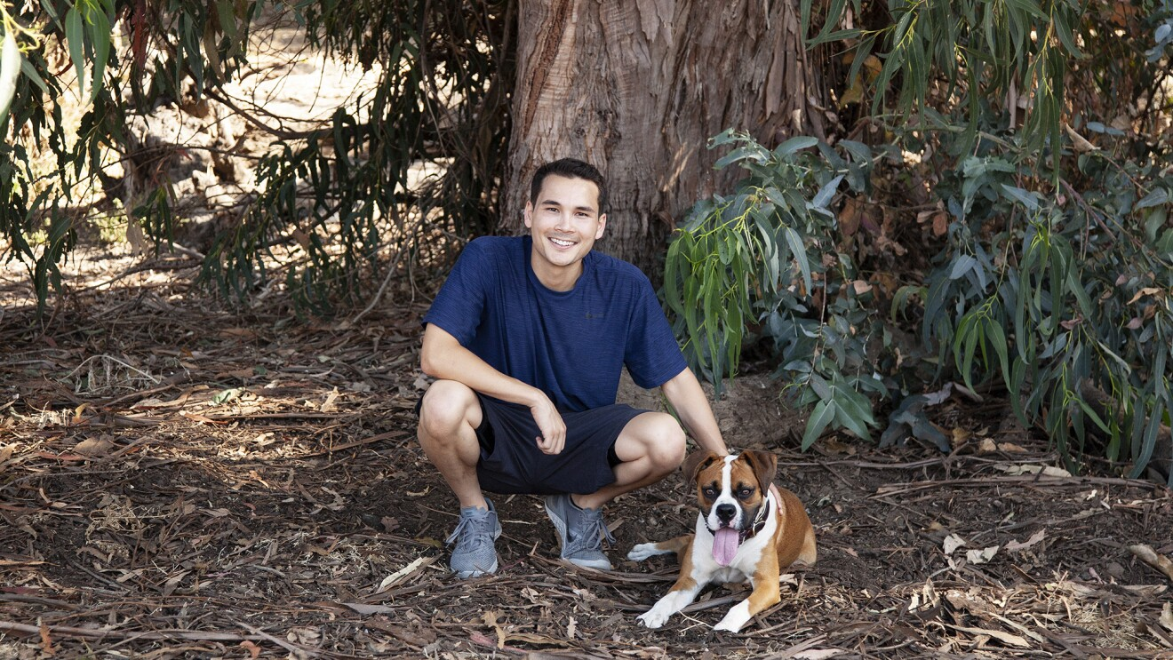 A man kneels next to his dog, in front of a large tree