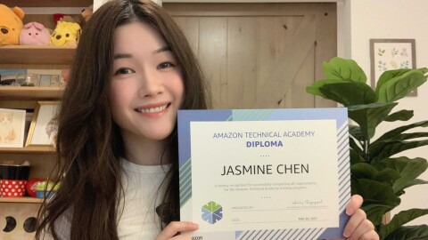 Jasmine poses with her ATA diploma. She has long dark hair wand wears a white long-sleeved shirt. There is a plant and drawings in frames behind her.