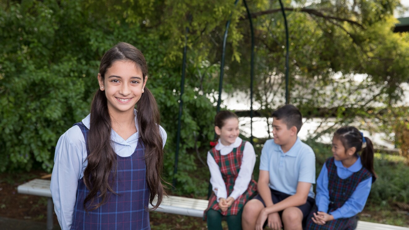 A young girl smiles and poses for the camera while three of her classmates sit behind her smiling at one another. They are outside surrounded by greenery and wear school uniforms.