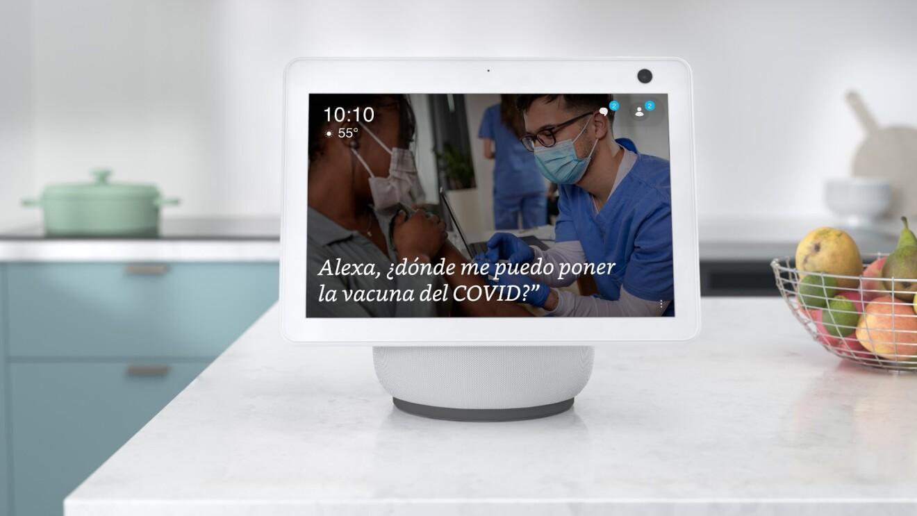 """Un dispositivo Alexa está colocado en la encimera de una cocina blanca y la pantalla dice """"Alexa, ¿dónde puedo obtener una vacuna contra el COVID-19?"""" Hay una canasta de alambre llena de peras, limas y manzanas junto al dispositivo."""