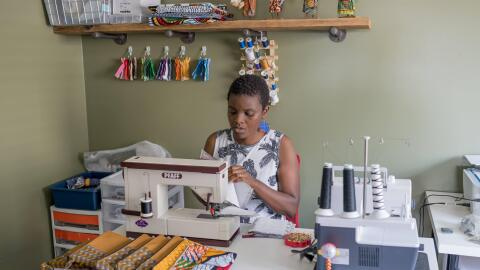 Amazon Maker Thrify Upenyu sits at a sewing machine working on colorful handmade clutches.