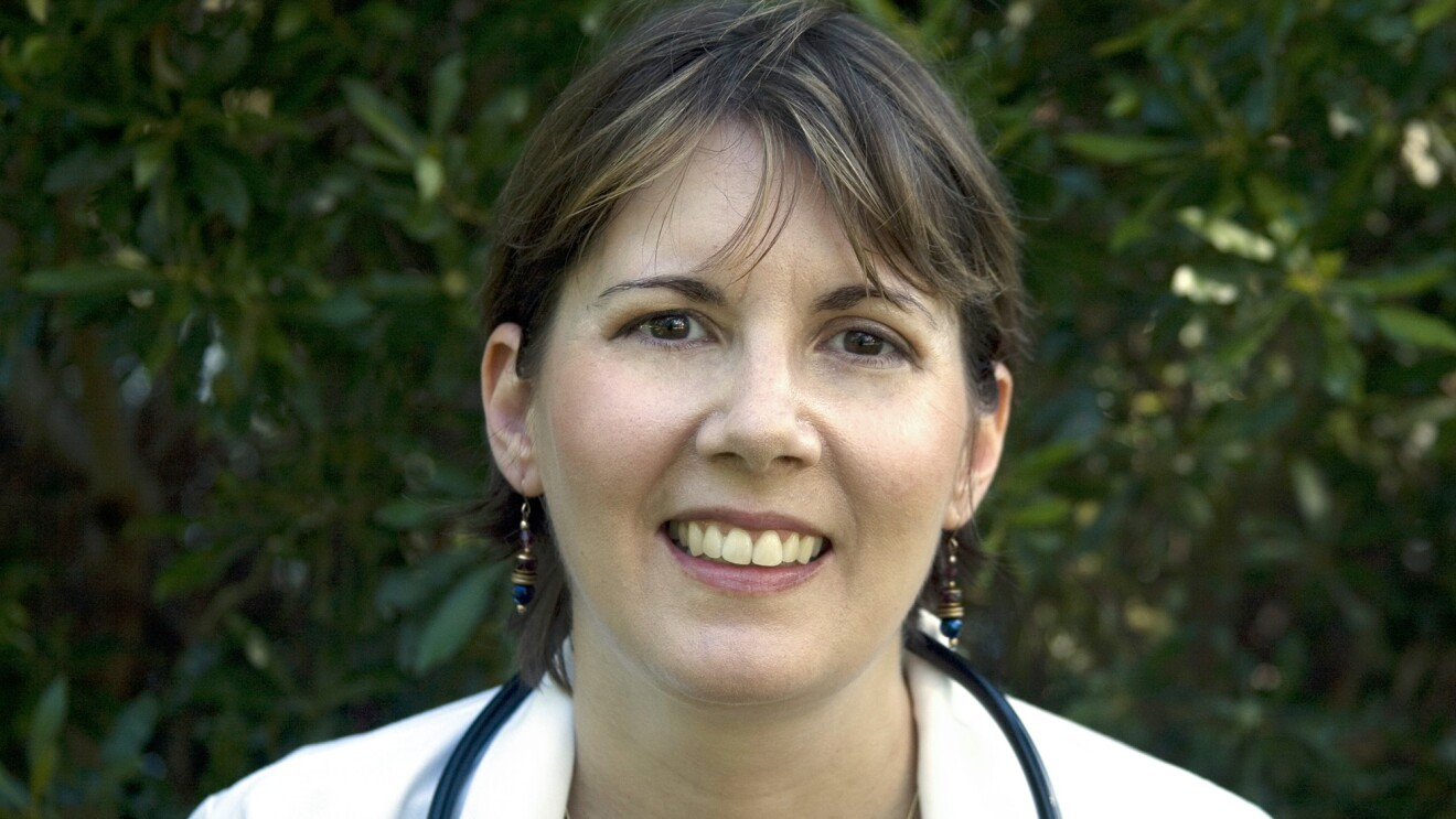 Amazon author CJ Lyons smiles into the camera. She has dark hair and is wearing a white jacket with a stethoscope around her neck. The background is blurred trees.