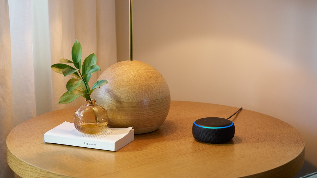 A new Echo Dot device on a side table, next to decorative objects.