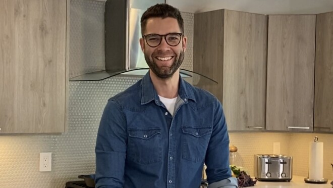 An image of Alexander E., Founder & CEO of Prepdeck, standing in a kitchen while smiling for a photo.