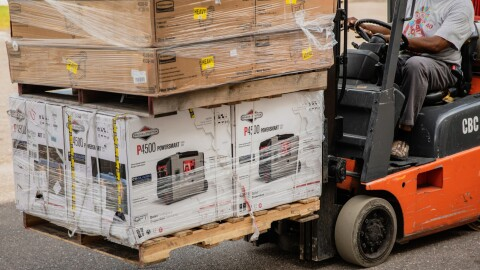 A man working with Amazon's disaster relief team is driving a forklift loaded with generators at the front. These generators will be used to provide power to those affected by recent natural disasters in the U.S.
