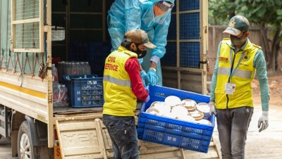 Two persons unloading relief material which will aid the commuity during COVID