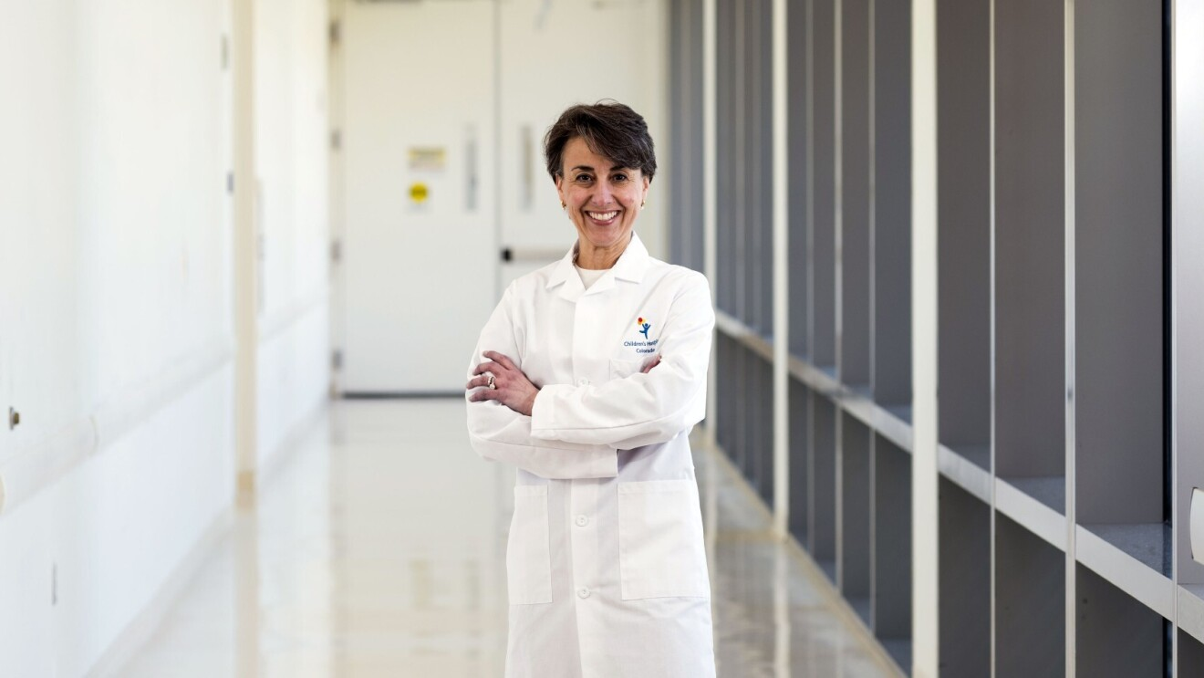 Childhood cancer researcher, Dr. Lia Gore, stands in the hallway of Children's Hospital Colorado smiling for the photo in her white doctors' coat.
