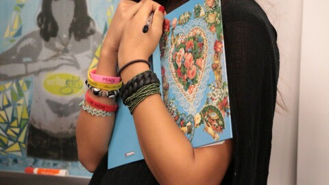 An image of arms holding an open book. The person is wearing a variety of bracelets showing their personality.