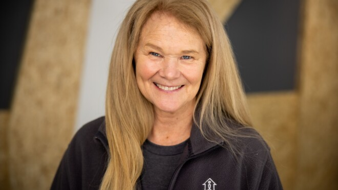 An image o a woman smiling for a headshot photo wearing a jacket with the Mary's Place logo on it.