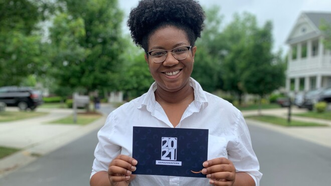 An image of a woman smiling for a photo on a street in her neighborhood while holding a paper invitation to Amazon's 2021 internship class.