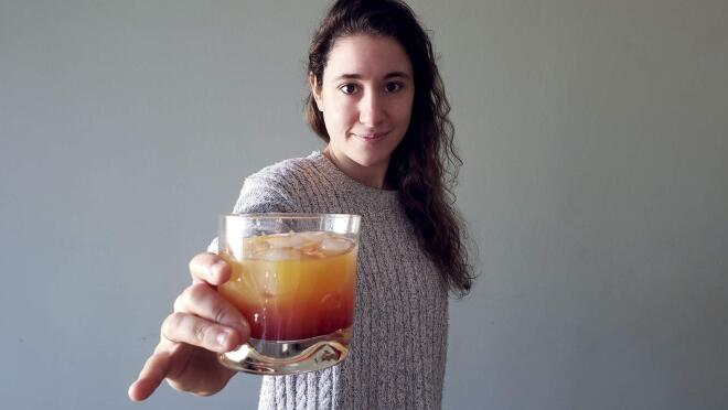 An image of a woman holding a cocktail glass out toward the camera while softly smiling.