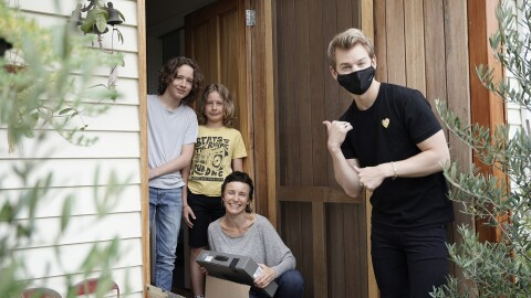 """A man stands by the front door of a home, he wears a black mask and black outfit, looking at the camera, he has his hand in a gesture that suggests """"look at that / them,"""" toward a family smiling at the camera."""