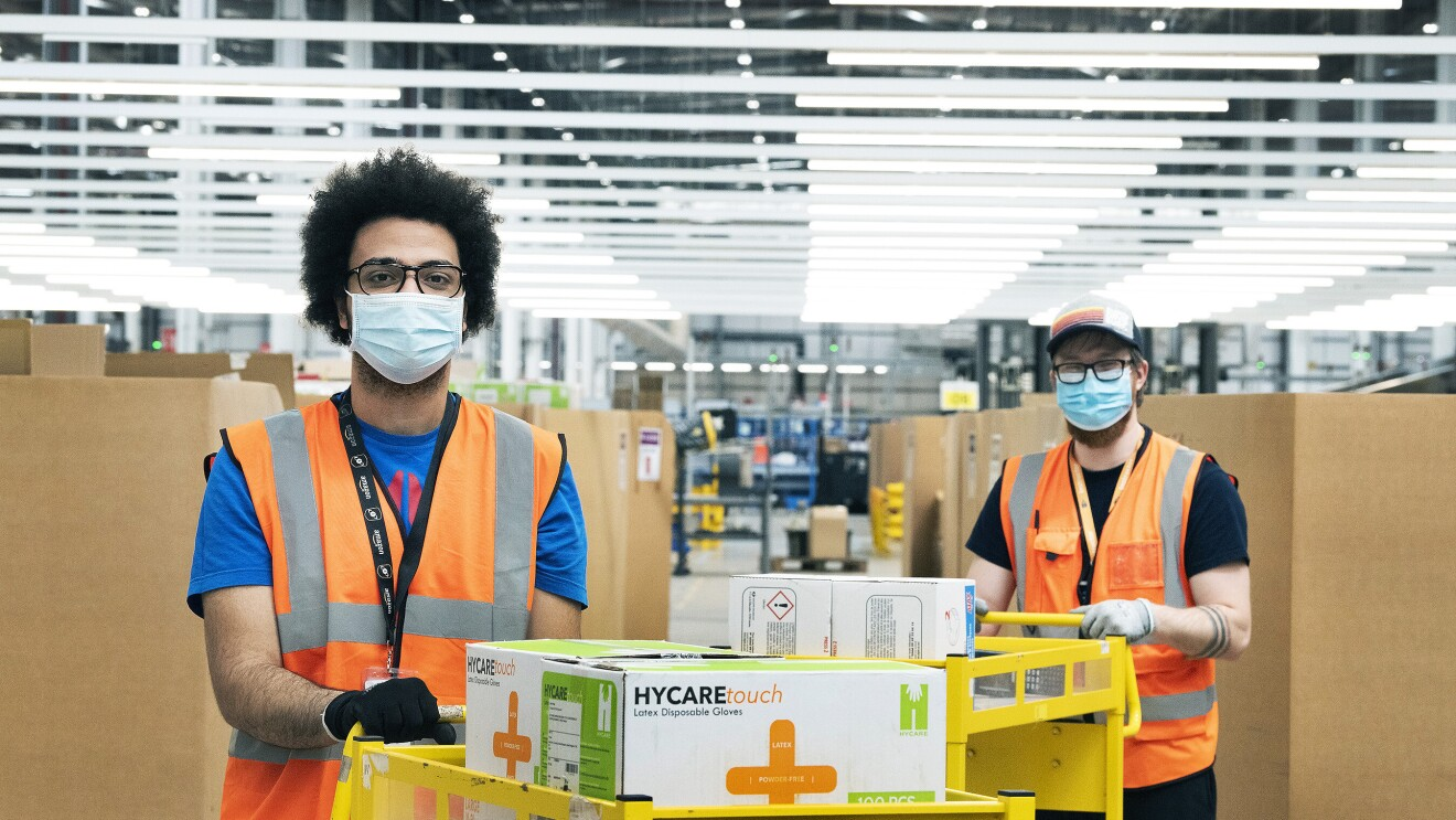 Amazon employees in a fulfilment centre packing medical supplies ready for the government into boxes. They are wearing hi-vis jackets and face masks.