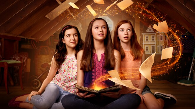 Three girls sit together. One holds a glowing book with pages flying out of it.