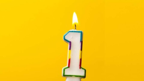 A yellowish-gold background with a lit number 1 candle.