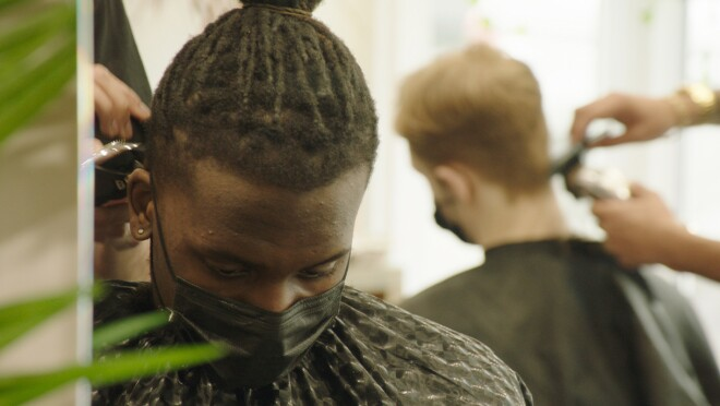An image of a man wearing a mask while getting his hair cut.